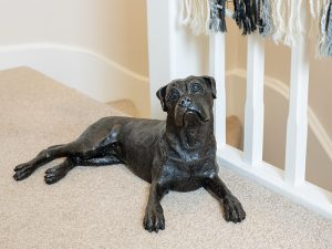 A cast resin urn in the shape of a boxer dog laying down looking upwards