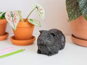 A resin figurine urn sculpted into the shape of a generic breed guinea pig. Available in an antique bronze style.