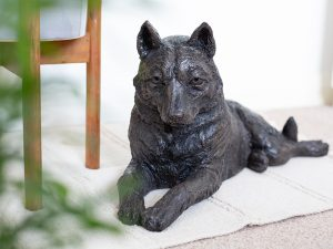 A resin figurine urn sculpted into the shape of a husky dog laying down. Finished in an antique bronze style.