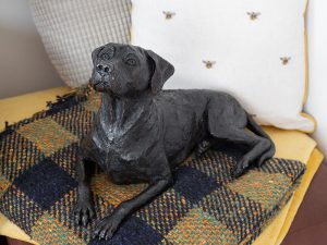 A resin figurine urn sculpted into the shape of a Rhodesian ridgeback laying down. Finished in an antique bronze style.