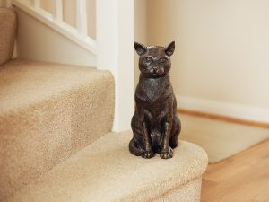 A cast resin urn in the shape of a generic cat breed sitting