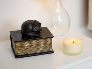 A small cast urn in the shape of a sleeping cat laying on top of a closed book with gold pages