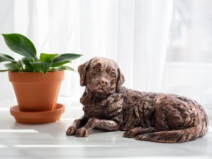 A resin figurine urn sculpted into the shape of a golden retriever laying down on a base. Available in an antique bronze style. A smaller version of the urn is available in a copper plated finish.