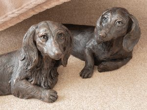 A cast resin urn of a short-haired and long-haired dachshund dog laying down