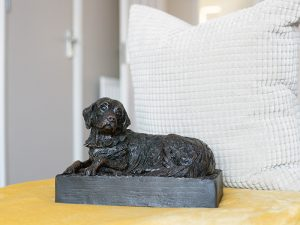 A small cast resin urn of a golden retriever dog laying down