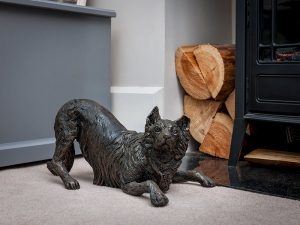 A cast resin urn in the shape of a border collie dog in a playful stance