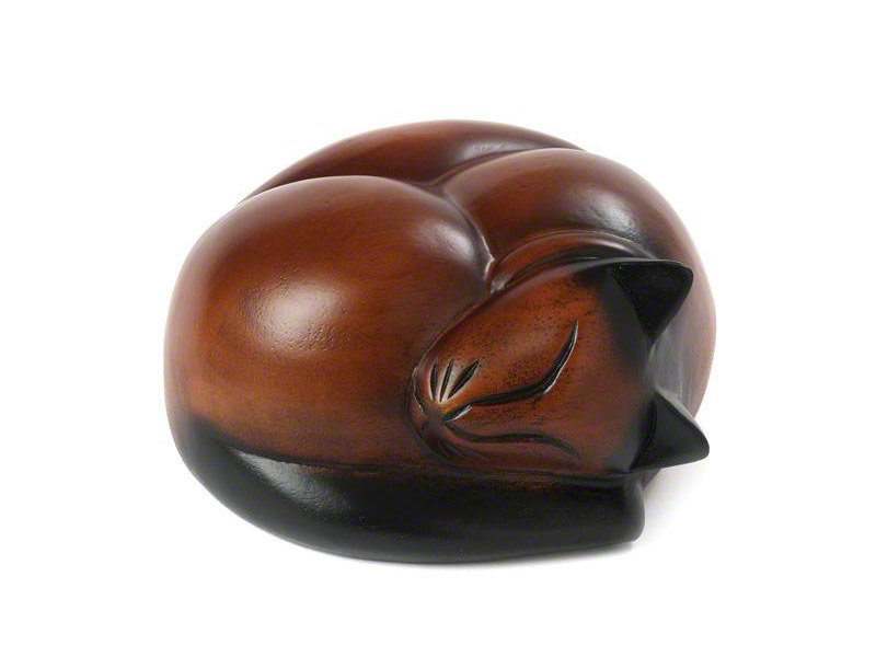 A peaceful wooden urn carved into the shape of a sleeping cat available in brown, brown colourpoint and black. A small and tactile urn just the right size to place in a special spot in memory of your feline friend.