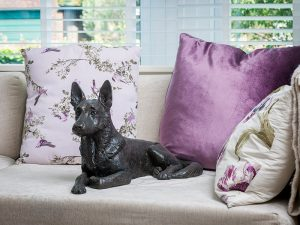 A cast resin urn of a german shepherd dog laying down