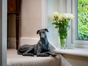 A cast resin urn of a greyhound dog laying with its front paws crossed looking to its right
