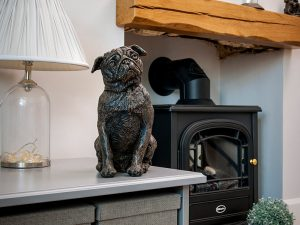 A cast resin urn of a pug dog sitting down looking forward