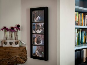 A photo frame with four photographs vertically with a concealed ashes container behind
