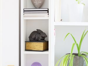 A resin figurine urn sculpted into the shape of a generic breed rabbit sitting on a book. Available in an antique bronze and gilt style.