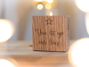 A square oak block with engraved wording on one side and a tealight holder in the top
